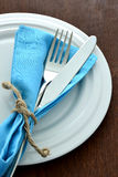 Fork and knife in tablecloth on dish. Stock Image