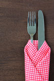Fork and knife in tablecloth on wooden background. Stock Photos