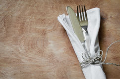 Fork and Knife Tied on White Napkin on Wooden Table. Table Setting, Royalty Free Stock Images