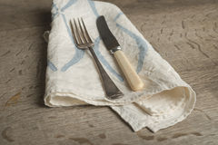 Fork and Knife on White Napkin with Blue Concave Lines Stock Photo