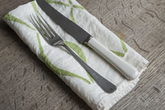Fork and Knife on White Napkin with Green Concave Lines Stock Photo