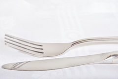 Fork and knife on a white napkin Stock Images