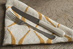 Fork and Knife on White Napkin with Orange Concave Lines Royalty Free Stock Photography