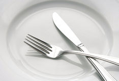 Fork and knife on a white plate Stock Photography