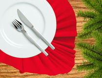 Fork, knife and white plate on a red cloth and christmas tree on Royalty Free Stock Photography