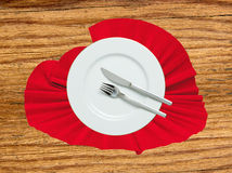 Fork, knife and white plate on red cloth on wooden table Royalty Free Stock Image