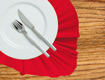 Fork, knife and white plate on a red cloth on wooden table Royalty Free Stock Photo