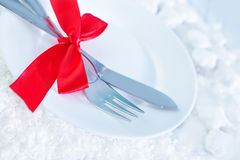 Fork and knife on white plate Royalty Free Stock Images