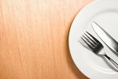 Fork and knife with white plate on wooden background Stock Image