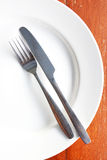 Fork and knife in white plate on wooden table. Royalty Free Stock Photos
