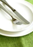 fork and knife on white plates Royalty Free Stock Photo