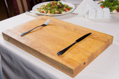 Fork and Knife on Wooden Chopping Board Stock Photos
