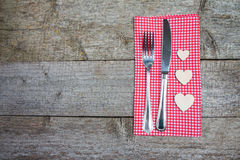 Fork, knife and wooden hearts on a red checkered napkin. Table setting for Valentine`s Day or wedding. Space for your text Stock Photography