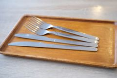 Fork and knife on a wooden plate. stock photos