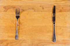 Fork and Knife on Wooden Surface Royalty Free Stock Images