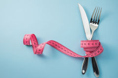 Fork And Knife. Knife and fork wrapped in tape measure on blue background stock images