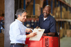 Fork Lift Truck Operator Talking To Manager In Warehouse Royalty Free Stock Photography