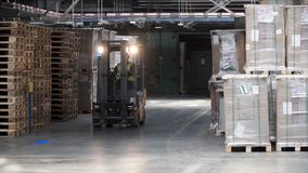 Fork lifter work in big warehouse. Clip. Warehouse man worker with forklift. Warehouse Rack of the Company stock image