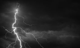 Fork lightning striking down during summer storm. In black and white Royalty Free Stock Photography