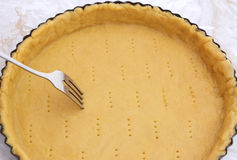 Fork making holes in a raw pastry case. Metal fork makes holes in a raw pastry case in a metal baking tin Stock Image