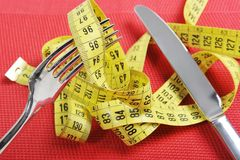 Fork in measure tape in diet and overweight concept Stock Images