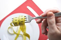 fork in measure tape in diet and overweight concept Stock Photos