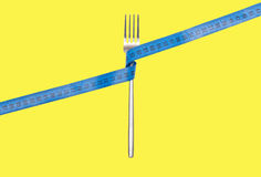 Fork and measuring tape on Yellow background Royalty Free Stock Photography