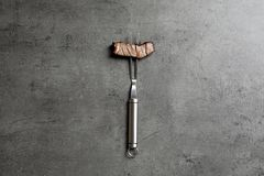 Fork with piece of delicious barbecued meat on gray background. Top view royalty free stock photo
