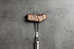 Fork with piece of delicious barbecued meat on gray background. Top view royalty free stock photography