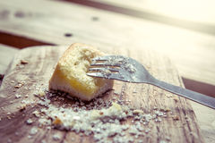 Fork on piece of sweet toast with sugar on wooden plate Stock Image