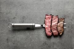Fork with pieces of delicious barbecued meat on gray background. Top view royalty free stock photography