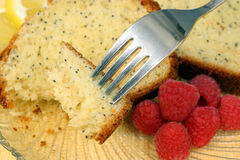 Fork Piercing Lemon Cake. Macro shot of a fork piercing lemon poppyseed cake  with fresh raspberries Stock Photography