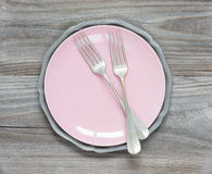 Fork on an pink plate. Two vintage fork on an empty pink plate Royalty Free Stock Images