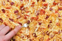 Fork in the pizza. Man hand pins a pizza with a fork, close-up, like a background Stock Photography