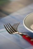 Fork and plate. Evening sun on fork casts shadow on dinner table Stock Photos