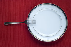 Fork and Plate. Fork and porcelain plate over red (copy space in the plate Royalty Free Stock Image
