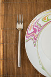 Fork and Plate on Bamboo Mat Stock Photography