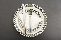 Fork plate and knife on a table Royalty Free Stock Photo
