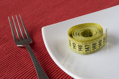 Fork, plate and a measure tape Stock Photography