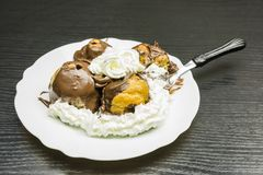 Fork with a portion of Profiterole with whipped cream. Fork with a chewed portion of Profiterole with whipped cream on a white plate on a wooden table Royalty Free Stock Images