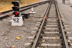 Fork in the railway tracks with red light semaphore. Railway in the city; Perspective stock image