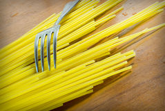 Fork and raw spaghetti on the table Stock Image