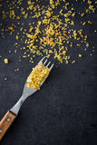 Fork with remains of couscous on black stone Stock Image