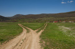 Fork in the road. And the village and the mountains Royalty Free Stock Photography