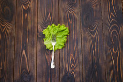 Fork on Salad Leaf. Fork on green salad leaf on table. flat lay. top view Stock Photo