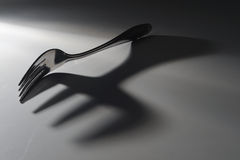 Fork and shadow. A fork casting a large shadow due to the back lighting Royalty Free Stock Images