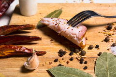 Fork with a slice of bacon on board herbs. Dried chilli pepper and bay leaf Stock Image