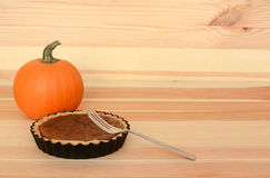 Fork with a small pumpkin pie on wood Royalty Free Stock Photography