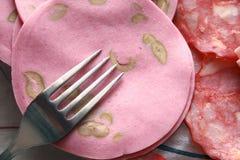 Fork sobre el jamón rebanado redondo Fotografía de archivo libre de regalías