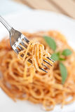 Fork with spaghetti with tomato sauce and basil Royalty Free Stock Image